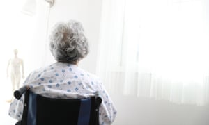 Woman in hospital gown, in wheelchair