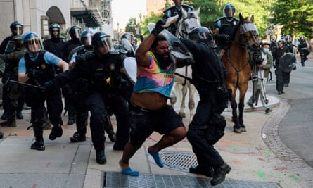Riot police chase a man as they clear protesters from Lafayette Park in Washington DC.