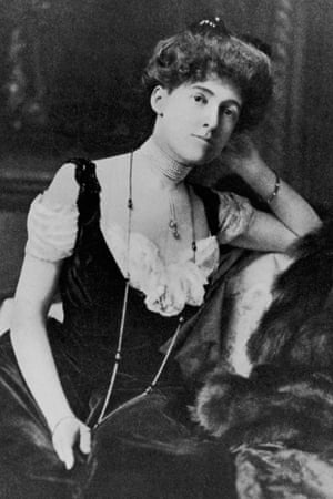 Portrait of American author Edith Wharton (1862-1937) sitting with one arm propped on the back of a sofa, wearing a long necklace