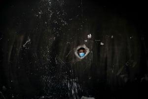 Man looks through hole in blackened wall