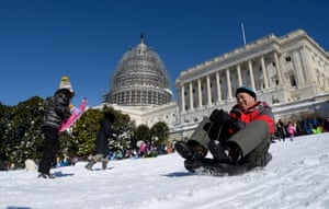 People sledge down the west lawn of the US Capitol in Washington