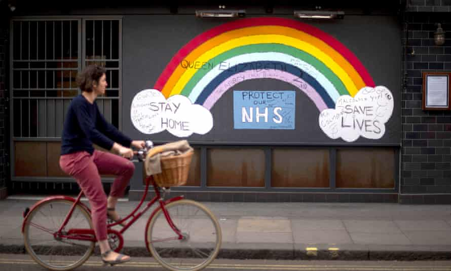 A woman cycles past a rainbow graffiti in support of the NHS in London's Soho in May 2020.