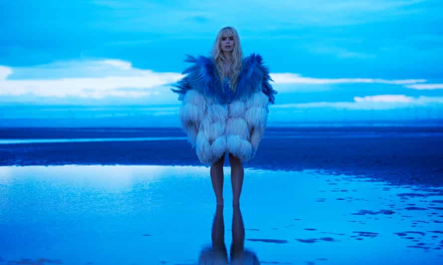 paloma faith standing in a channel on a sandy beach in the twlight