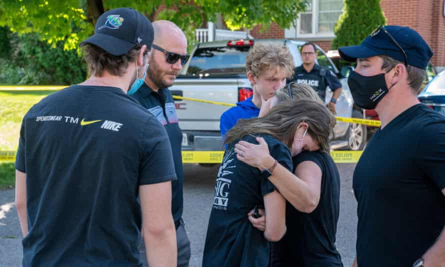 Friends of victims in a shooting at a home on Parklane Avenue in Oshawa, Ontario, react after laying flowers on Friday.