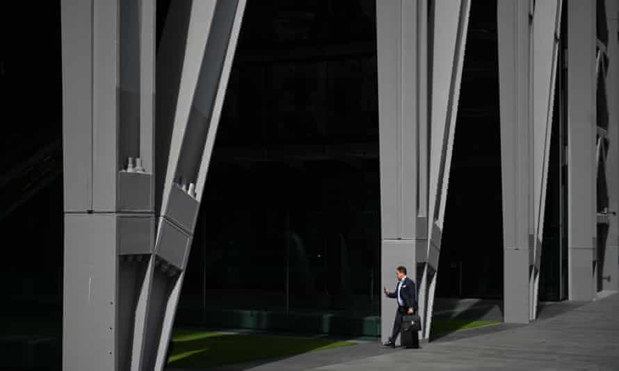 A man arrives at an office block in the City, London.