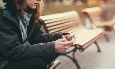 a girl holding a phone looking pensive while reading messages