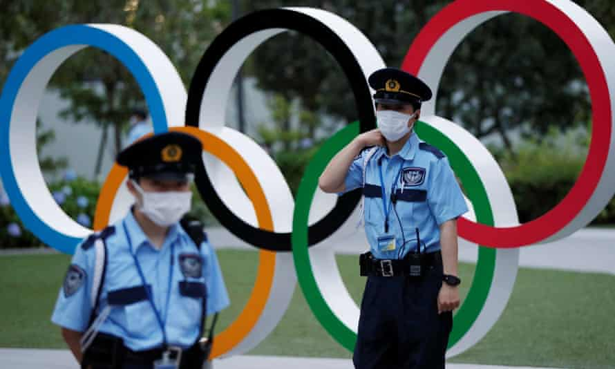 Security officers stand guard next to Olympic Rings monument