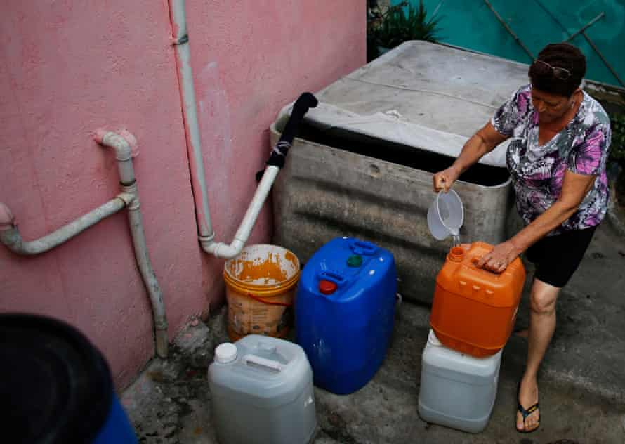 A resident of São Paulo's Brasilandia neighbourhood prepares rainwater to use in the bathroom and to clean the floor of her house.