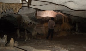 A researcher looks at drawings in a cave on Mona island