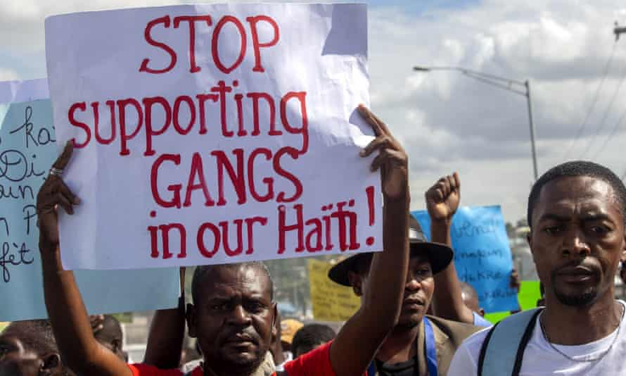 A protester holds a sign with a message to stop supporting gangs during a protest demanding the resignation of Haiti's President Jovenel Moïse in Port-au-Prince in December.