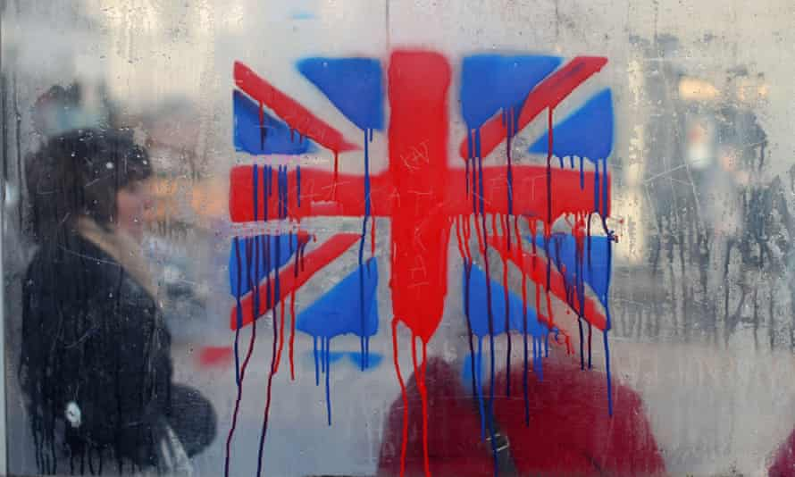 A painted union jack is seen as people wait at a bus stop in Belfast.