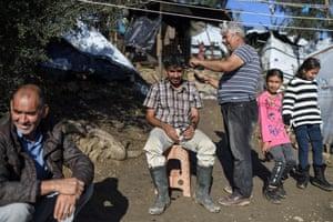 A man has his hair cut at the makeshift camp in Lesbos