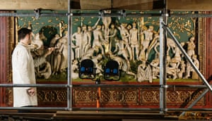 A conservator removes dirt and dust from two Victorian reredos in York Minster, England