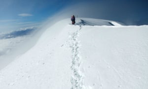 Aymara indigenous women climb through snowstorms and heavy winds at the Illimani mountain
