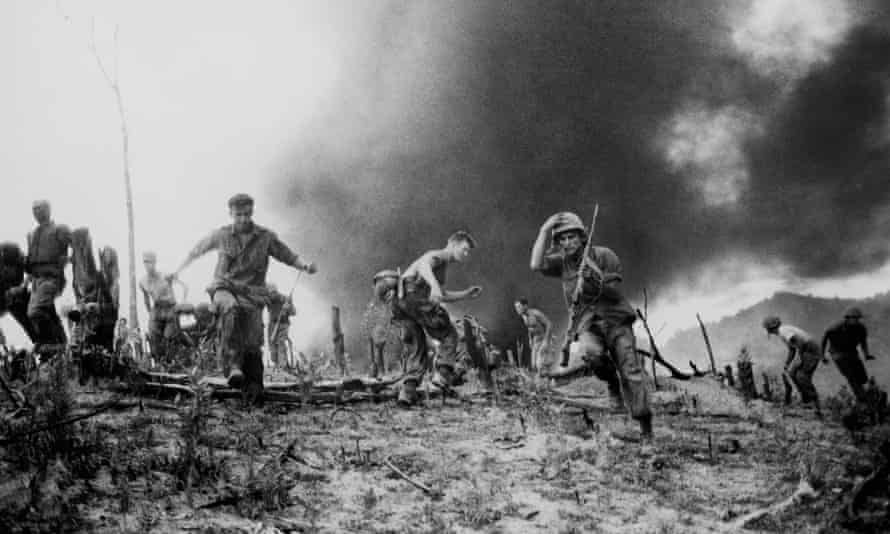 US troops in Vietnam scatter as a helicopter burns
