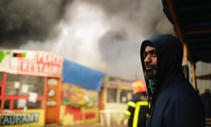 A man looks on as French authorities demolish the Calais refugee camp.