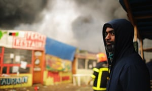 A man looks on as fires burn in the refugee camp in northern France.