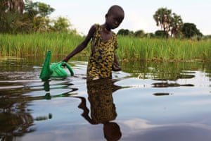A girl collects water in a plastic can in the Sudd Swamp near the town of Nyal, South Sudan.