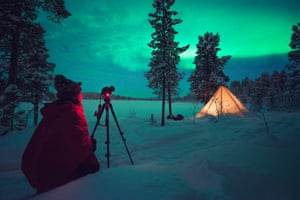 Taking photo of the northern lights in the snow, with Scandinavian Photo Adventures