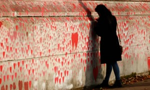 A woman writes a message onto the UK's national Covid memorial wall on the south bank footpath of the  Thames in London.