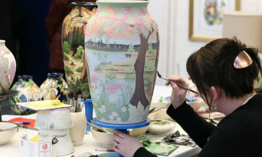 A worker at the Moorcroft Pottery in Stoke-on-Trent demonstrates the intricate skill of vase painting.