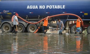 Municipal workers use a water truck to remove stagnant water from a neighbourhood in Chiclayo, Peru
