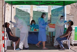 Medical workers take samples from citizens for Covid-19 test in the central Israeli city of Lod on 2 July, 2020.