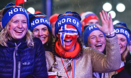 Close up of a group of female Norwegians at a ski event, with faces painted in the colours of the Norwegian flag.