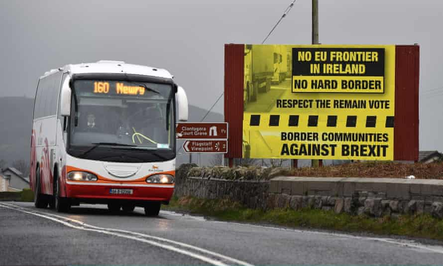 A bus crossing along the border between Northern Ireland and the Republic of Ireland passes a sign campaigning against a hard Brexit.
