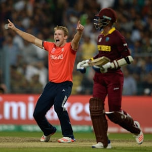 David Willey makes sure West Indies batsman Andre Russell walks off the field.