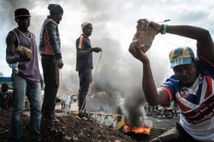 Opposition supporters hold up bricks as they block streets and burn tyres during a protest in Kisumu, Kenya