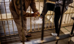 A prison guard closes the lock of an inmate's ankle chains at the male section of the Johannesburg Correctional Centre also known as Sun City Prison, South Africa, on April 8, 2020.