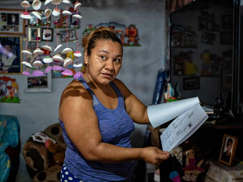 Esmeralda shows the drawings of how to build a home sewage system, which is what the Salvadoran water department is requiring for residents to have if they wish to be considered to have a potable water system in their home.