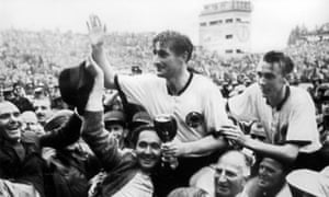 Fritz Walter, holding the Jules Rimet trophy, and Horst Eckel, right, are carried on the shoulders of their fans after the final.