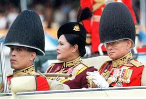 Thailand's King Bhumibol Adulyadej (R), Queen Sirikit (C) and Crown Prince Maha Vajiralongkorn (L) review troops, as part of celebrations for the King's 73rd birthday