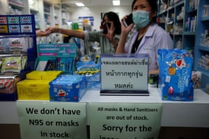 A sign in a Bangkok pharmacy states that protective face masks are out of stock
