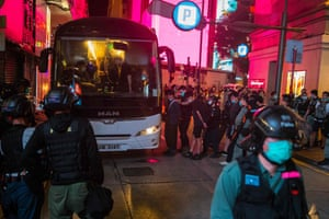 Police detain people on a bus after a rally