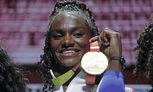 Dina Asher-Smith holds up her gold medal for the women's 200m at the World Athletics Championships in Doha