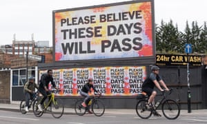 Cyclists passing a billboard in east London saying 'These days will pass'.