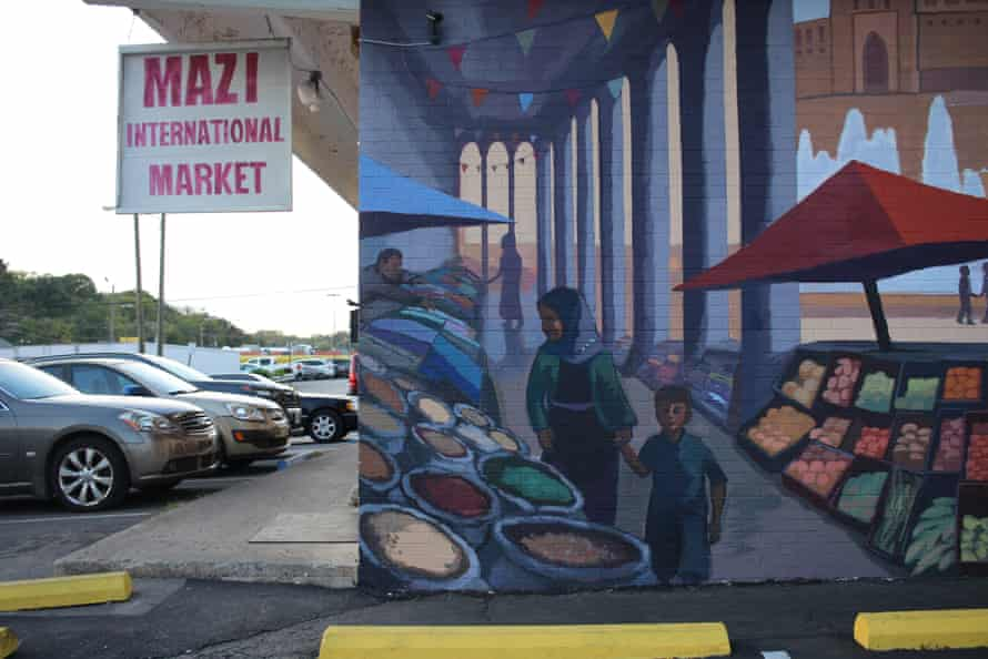 A mural depicting scenes of traditional Kurdish life is painted on the side of a Kurdish grocer in Little Kurdistan, Nashville.