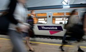 Commuters walk past a Thameslink train