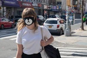 A woman wearing a comedy animal face mask walks down Knickerbocker Avenue in Brooklyn, US