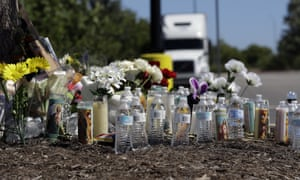 Flowers, candles, and bottles of water help create a makeshift memorial in the parking lot of a San Antonio Walmart store near where authorities Sunday discovered a tractor-trailer packed with immigrants in 2017.