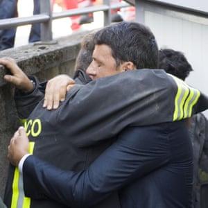 Renzi hugs a rescuer in Amatrice.