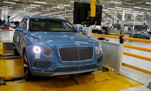 A worker drives a Bentley SUV on a rolling road at the factory in Crewe.