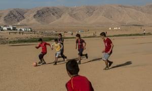 Yazidi boys play football at a camp in Sharya, Iraq