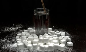 A cola carbonated drink surrounded by sugar cubes