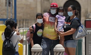 Visitors wearing masks pose for photos at the Alamo, which remains closed, in San Antonio, Texas.