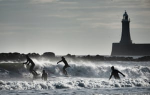 Tynemouth, UKSurfers silhouetted against the waves near North Shields