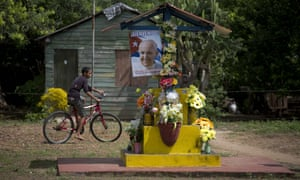 A boy rides his bike past a poster of Pope Francis on an altar near Taguasco, Cuba